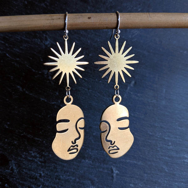 Moon & Milk - Golden raw brass earrings with a Picasso woman face figure and a sunburst charm. Always handcrafted with love.