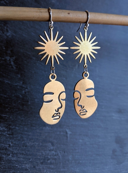 Moon & Milk - Raw brass Picasso face figure earrings with a sunburst charm