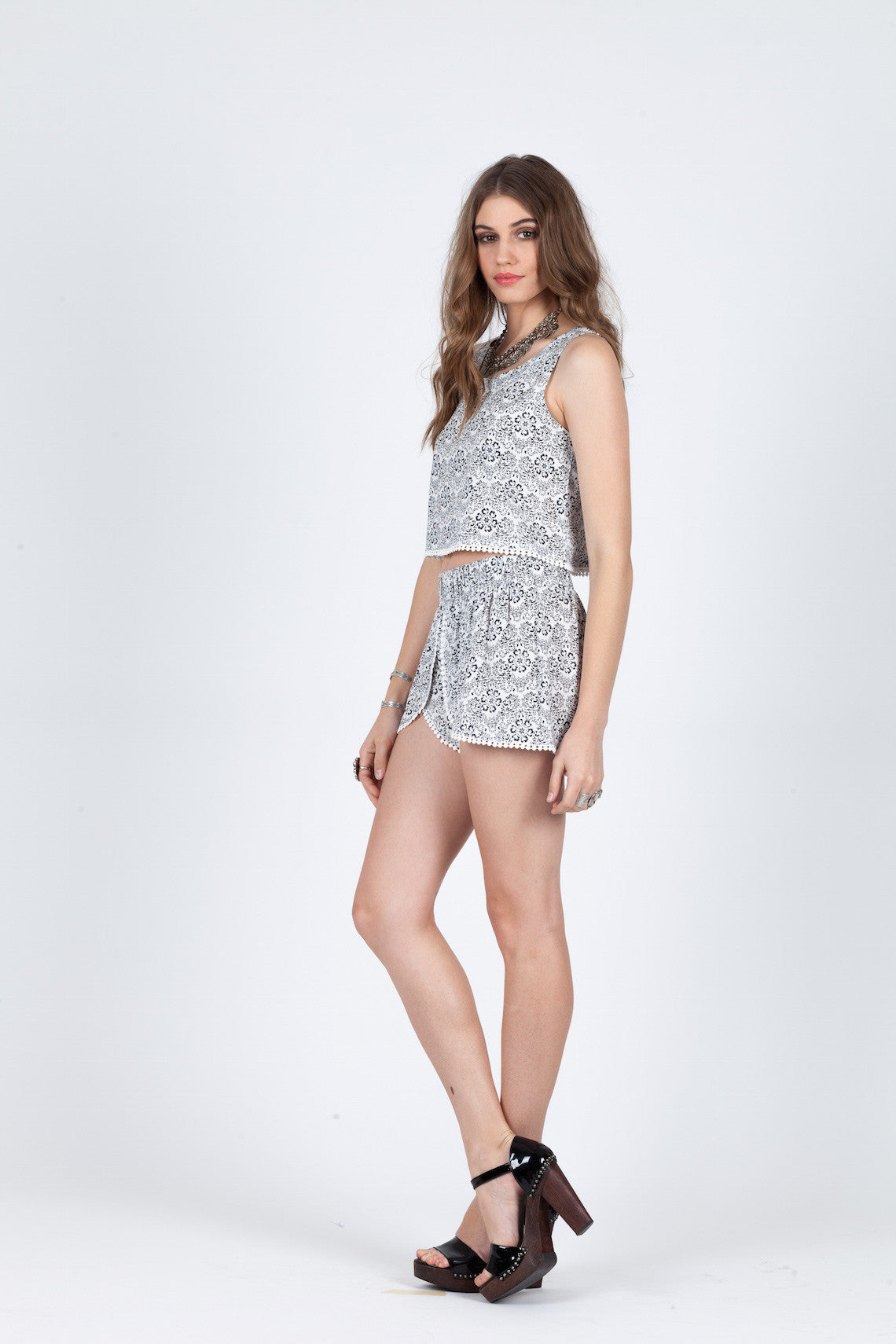 "Sweet & Simple Crop Top-Women - Apparel - Shirts - Blouses-Product Details 100% Viscose Pompom bottom hem detailing Shown with the Sweet & Simple Shorts Hand wash cold and lay flat to dry Model is wearing a size S Model is 5'9"" with 32"" bust, 24"" waist, and 34.5"" hips Easy Measure Conversion XS/0 S/1 M/2 L/3 US 0/2 2/4 6/8 8/10 AUS 4/6 6/8 10/12 12/14 BRAZIL 34/36 36/38 40/42 42/44 CHINA 76a/80a 80a/84a 88a/92a 92a/95a EUP 32/34 34/36 38/40 40/42 JAP 5/7 7/9 11/13 13/15 RUS 42 42/44 46/48 50/52"