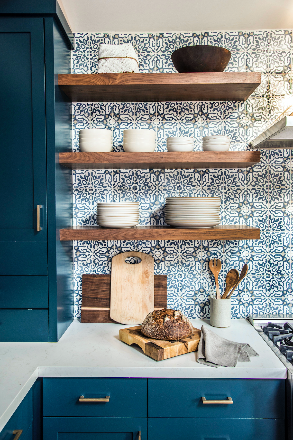 Styled shot of blue kitchen cabinets with gold hardware, tiled backsplash, with styled floating wood shelves and bread board.