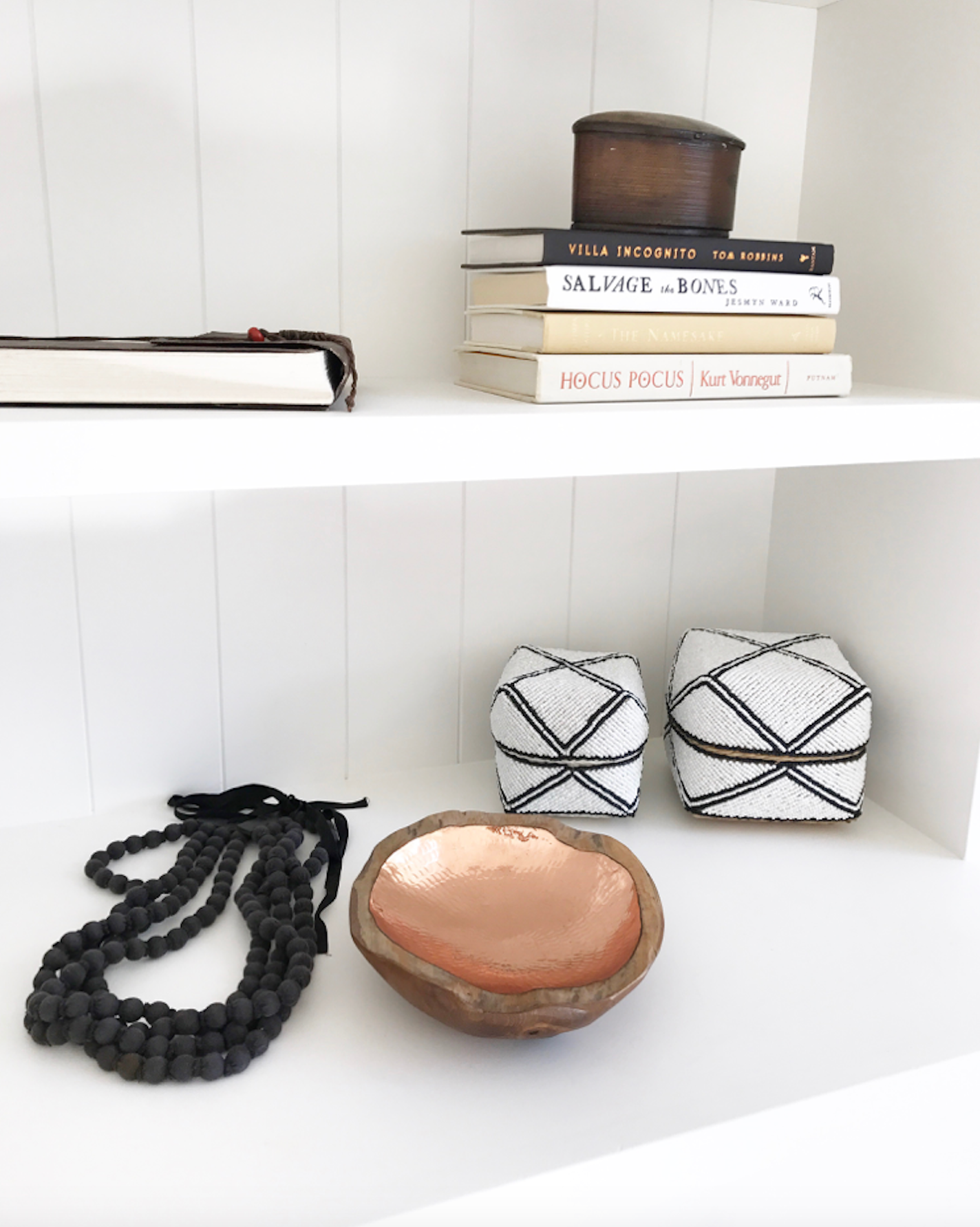 Styled white shelves with copper and teak bowl, beads, stacks of books, and black and diamond pattern beaded bali baskets.