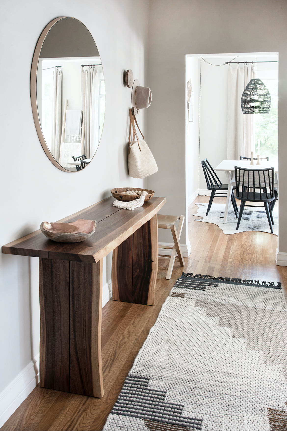 Marina Flat Entry vertical shot with bali beads, sisal hand bag, leather folding stool, round wall mirror, copper and teak bowl, wall hooks, woven rug and view of the adjoining dining room space.