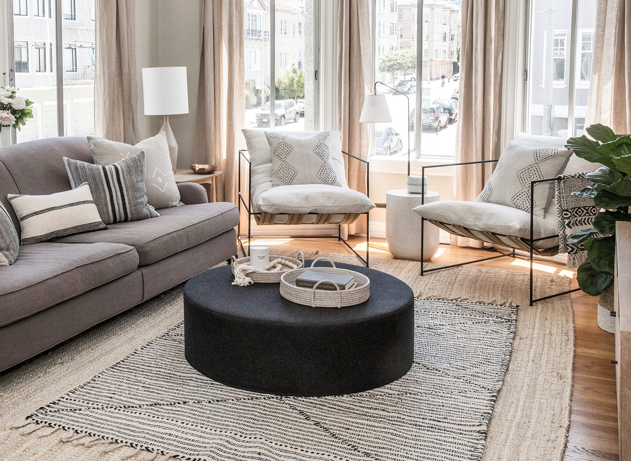 Marina Flat living horizontal room shot with black frame white cushion lounge chairs, traveled pillows, black fabric ottoman coffee table with bali beads and woven baskets, on top of handwoven Moroccan black and white rug.