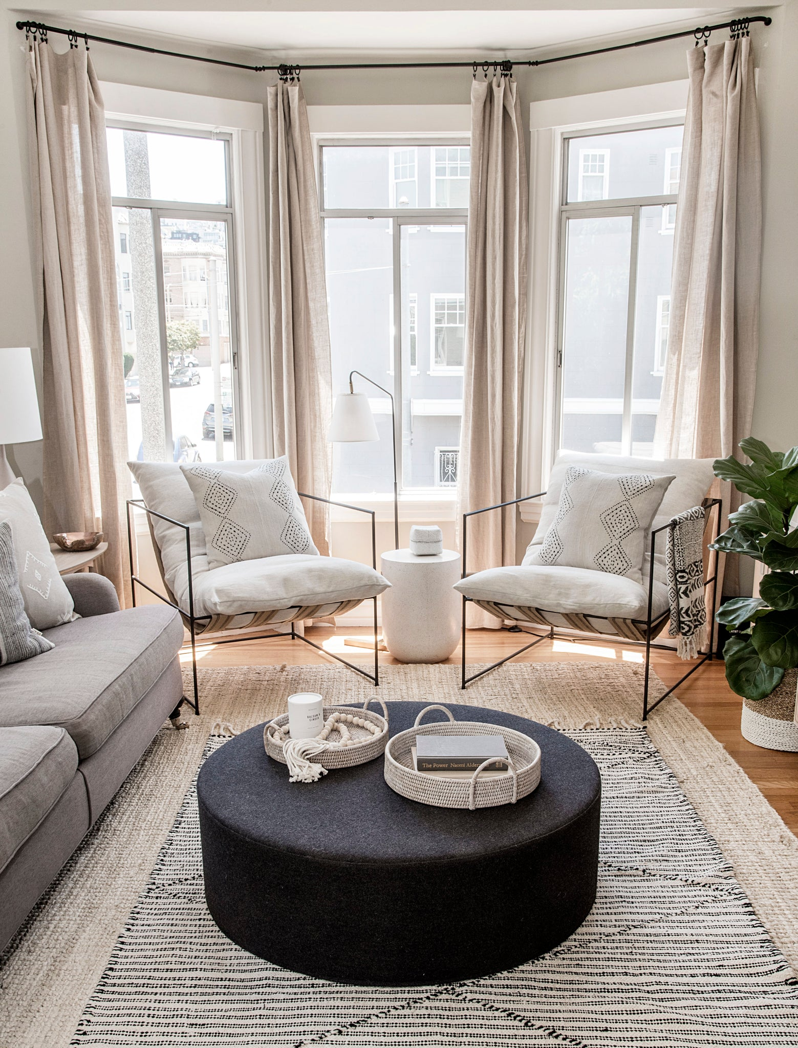 Marina Flat living room vertical shot with black frame white cushion lounge chairs and black fabric ottoman featuring bali beads, handwoven Moroccan area rug in black and white, traveled pillows, plant, and soft neutral palette.