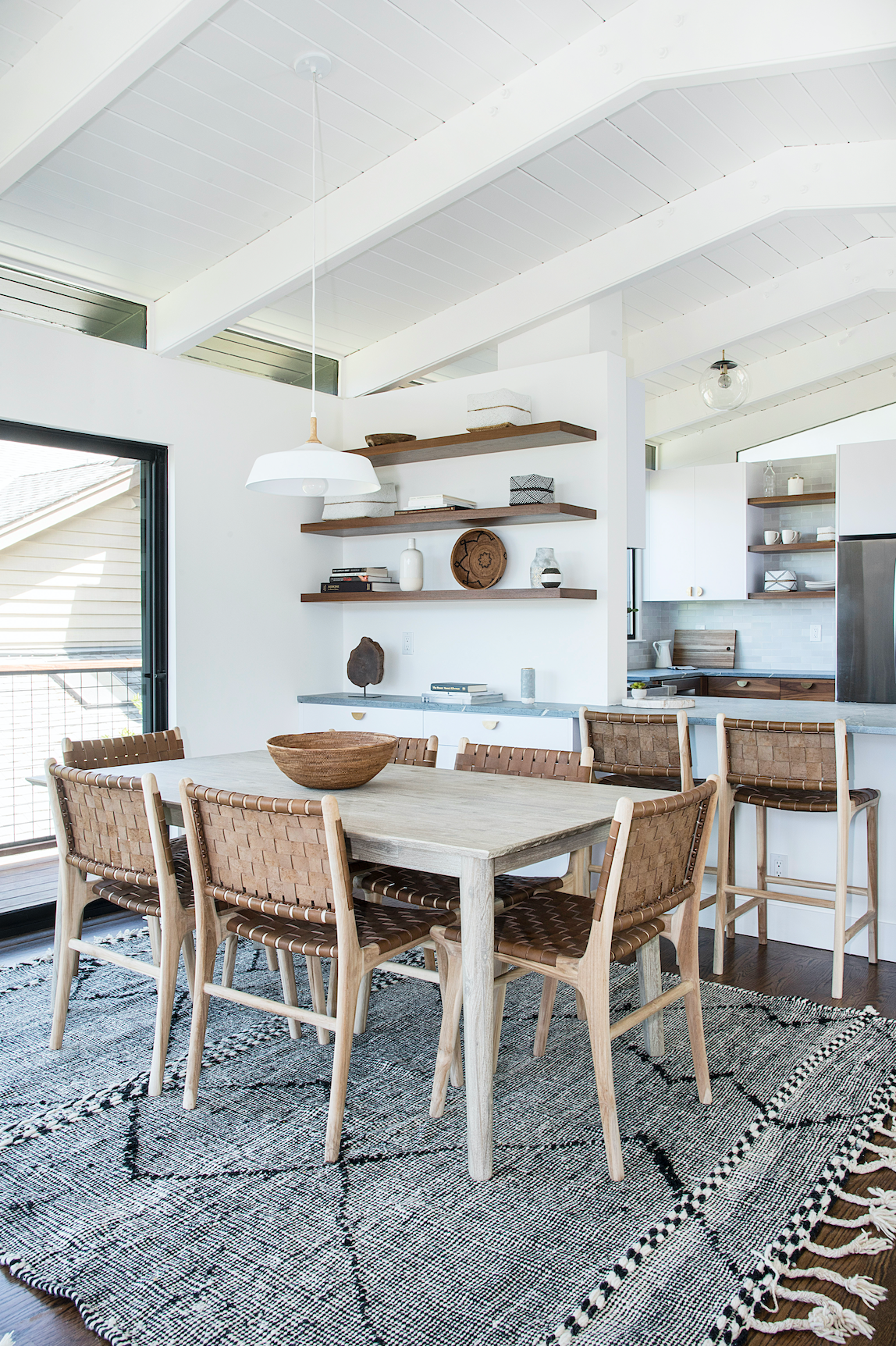 Dining room in Mill Valley Mid Century with woven leather strap dining chairs in beige with dark wood wall shelves featuring decor and slight view of kitchen area.