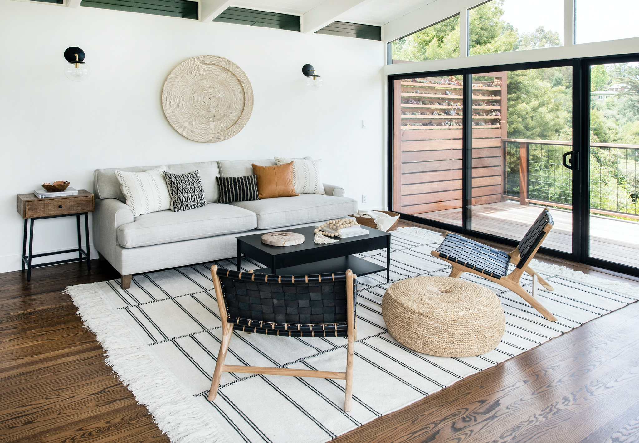 Living room area with natural woven poufs, black woven strap lounge chairs, striped rug, black coffee table, decor items, grey sofa, assorted pillow, white walls, wall sconces, sliding glass door, and hanging wall basket in Mill Valley Mid Century.