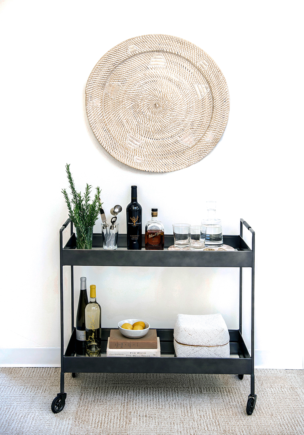 Styled bar cart shot in true Botanicals office with wine and plants below large woven wall basket hanging on wall.