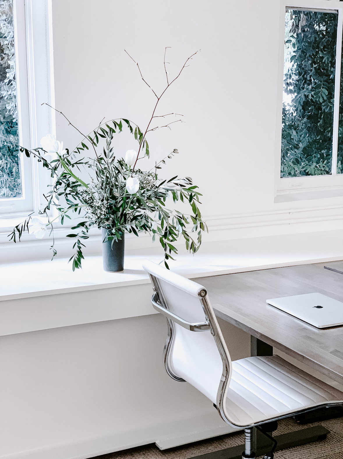 Styled shot from True Botanicals office of white office chair, wood table, laptop, and vase of flowers with white background.