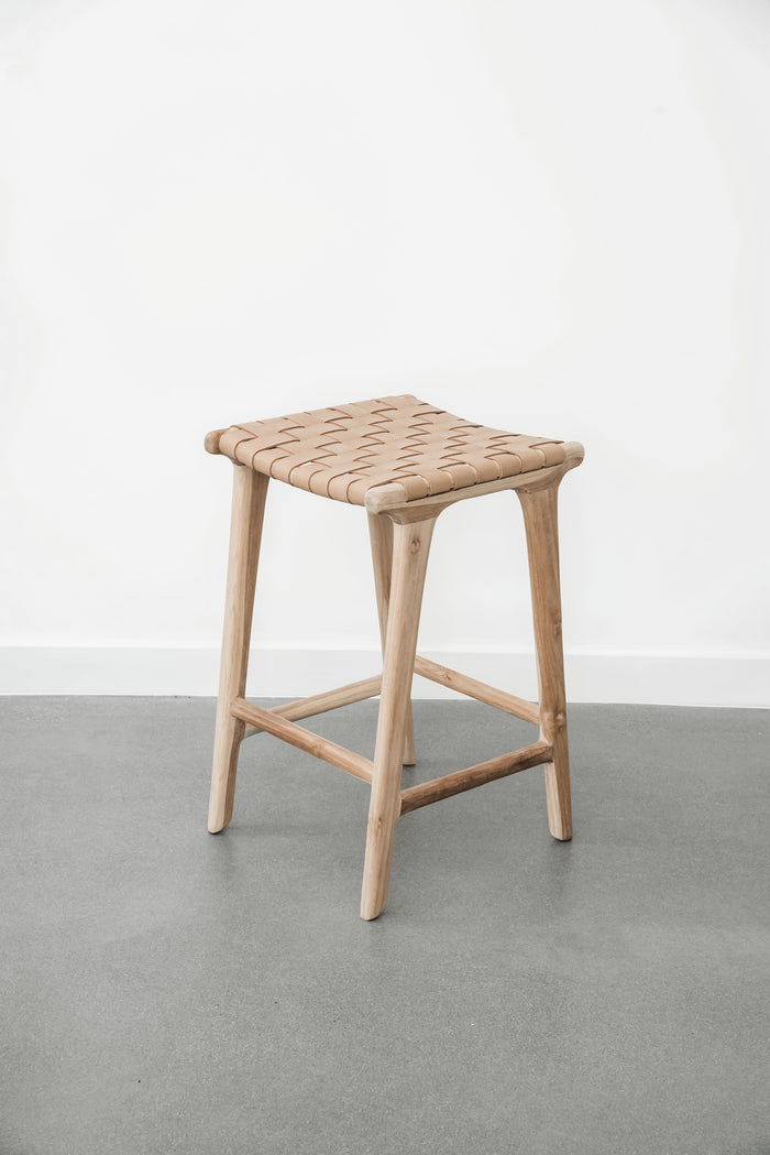 Comfortable, casual, leather-strapped counter height Backless Woven Leather Counter stool in Beige on a white background. Handmade in Bali using Teak wood and vegetable-tanned leather imported from Java. - Saffron and Poe