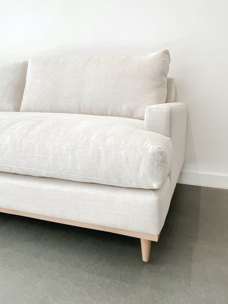 Angled close-up view of contemporary linen and oak sofa against white background on concrete floor.
