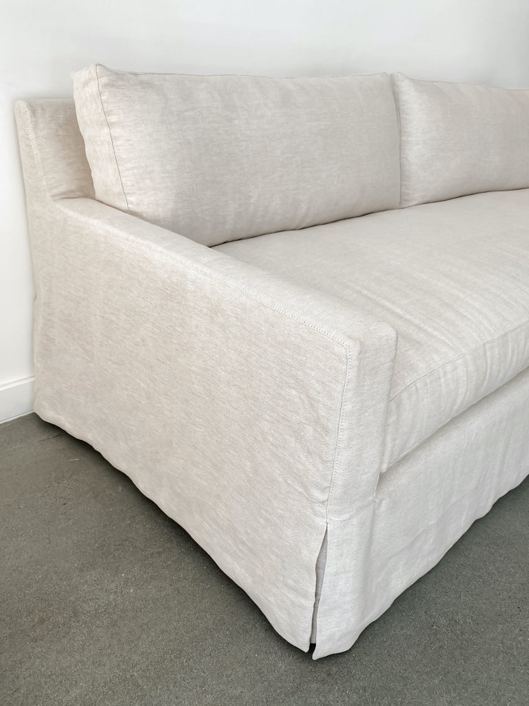 Angled close up of slipcovered sofa in natural linen fabric against white background and concrete floor.