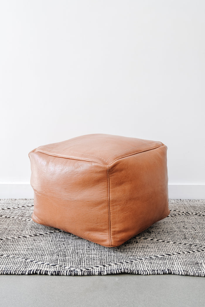 Angled view of Square Leather Moroccan Pouf on a Moroccan Kilim Rug against a white wall. - Saffron and Poe