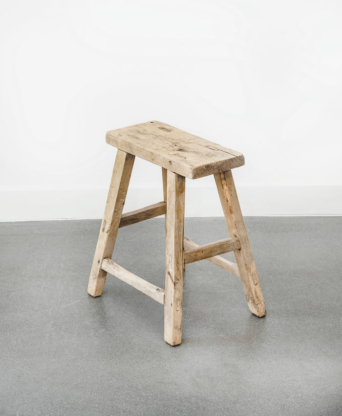 Angled view of vintage rectangular stool on concrete floor with white walls. - Saffron and Poe