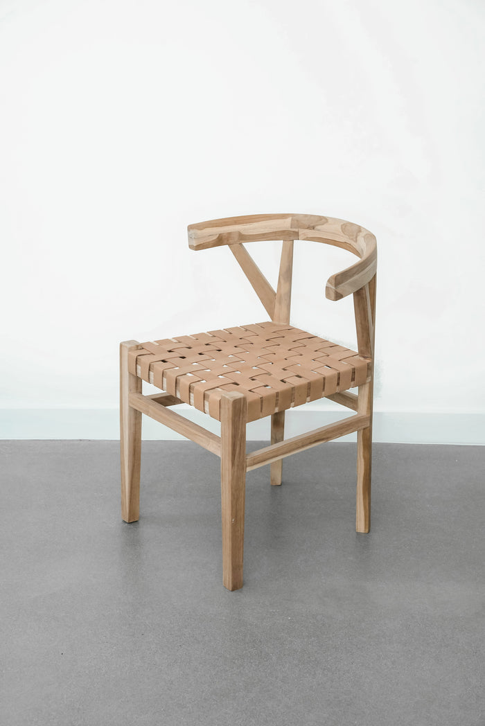 One curved wood and woven beige leather dining chair inspired by the wishbone Chair with white background. Handcrafted in Bali with Teak wood and vegetable-tanned leather imported from Java. - Saffron and Poe