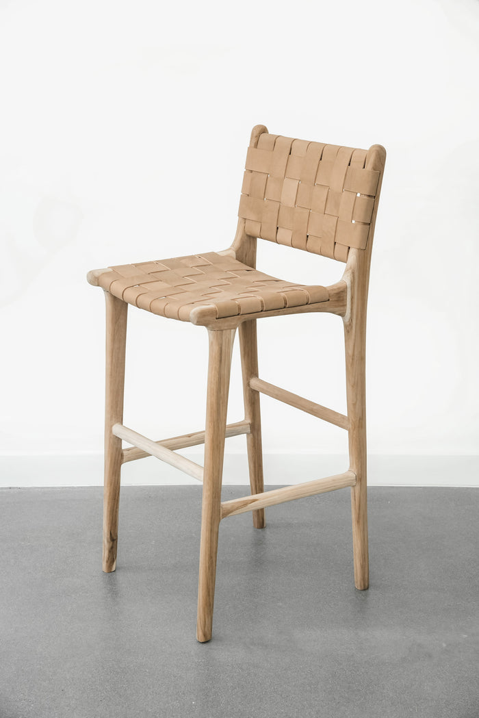 Side profile of our comfortable, casual, Woven leather strap bar stool in beige. Handmade in Bali using Teak wood and vegetable-tanned leather imported from Java. - Saffron and Poe