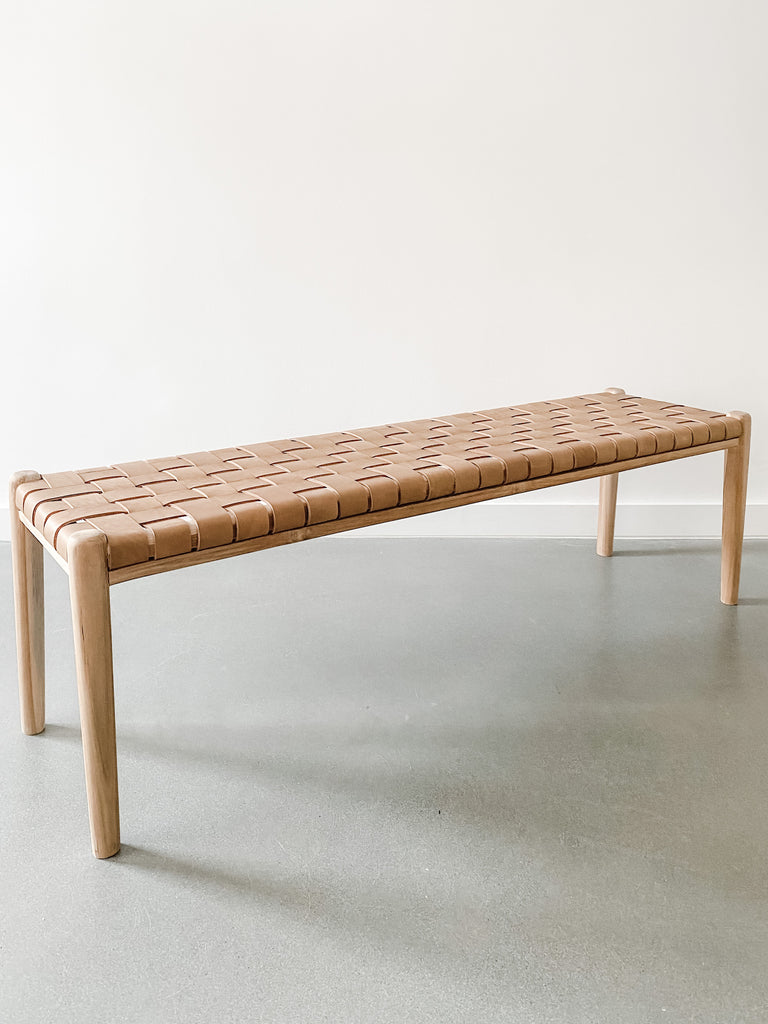 "Angled view of 60"" woven leather strap bench in beige against white background. Handcrafted in Bali. Teak wood and leather straps. - Saffron and Poe"
