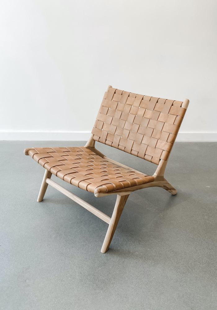 Angled view of Woven Leather Strap Lounge Chair in Beige against white background. Handcrafted in Bali. Teak wood and leather straps. - Saffron and Poe