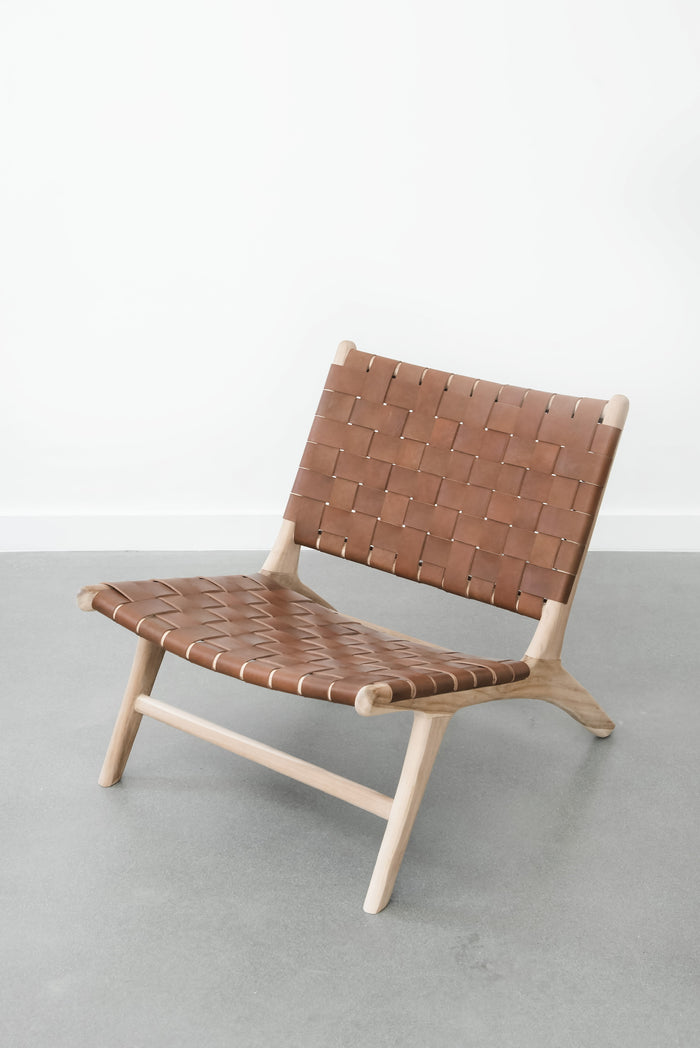 White background with our Woven Leather Strap Lounge Chair - Saddle. Handmade in Bali with Teak wood and vegetable-tanned leather imported from Java. - Saffron and Poe