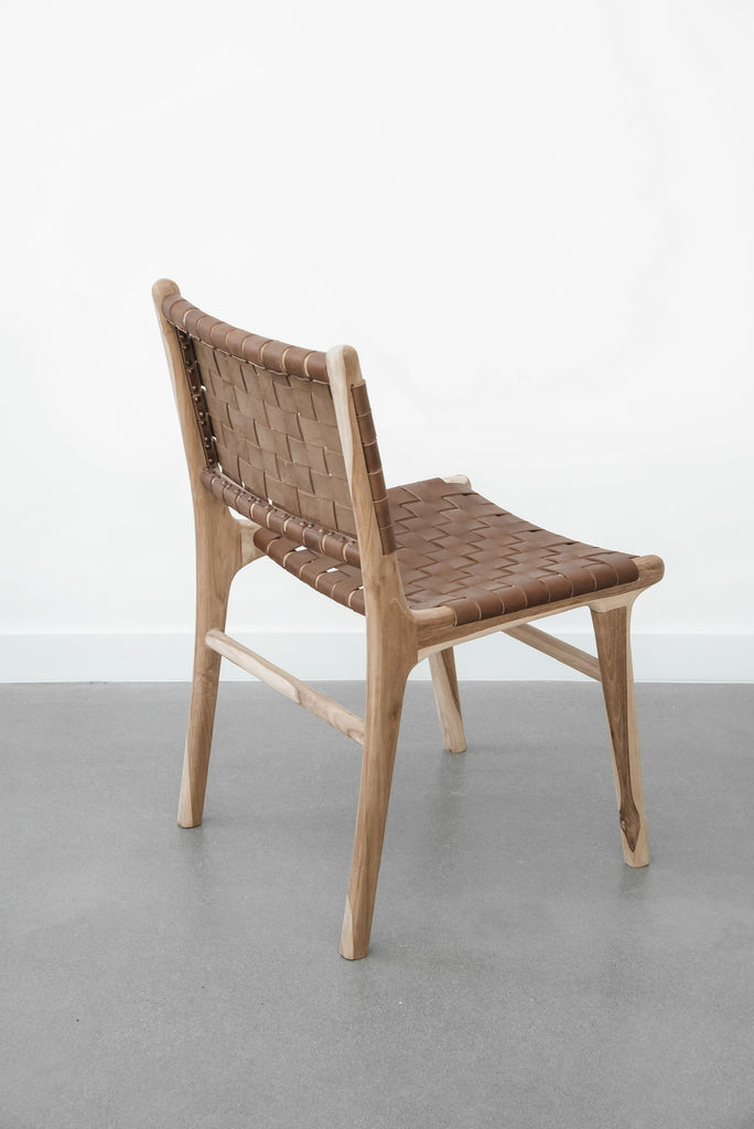 Side profile of our Woven Leather Strap Dining Chair - Saddle on white background. Handmade in Bali with Teak wood and vegetable-tanned leather imported from Java. - Saffron and Poe