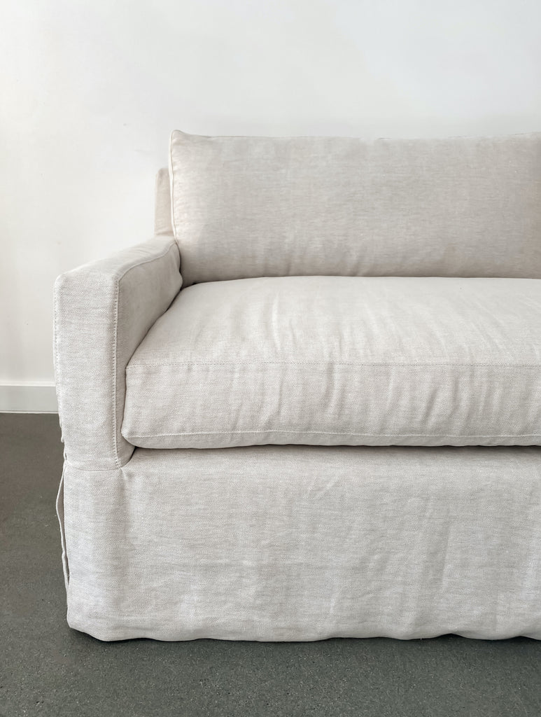 Close up view of slipcover sofa in natural linen fabric against white background and concrete floor.