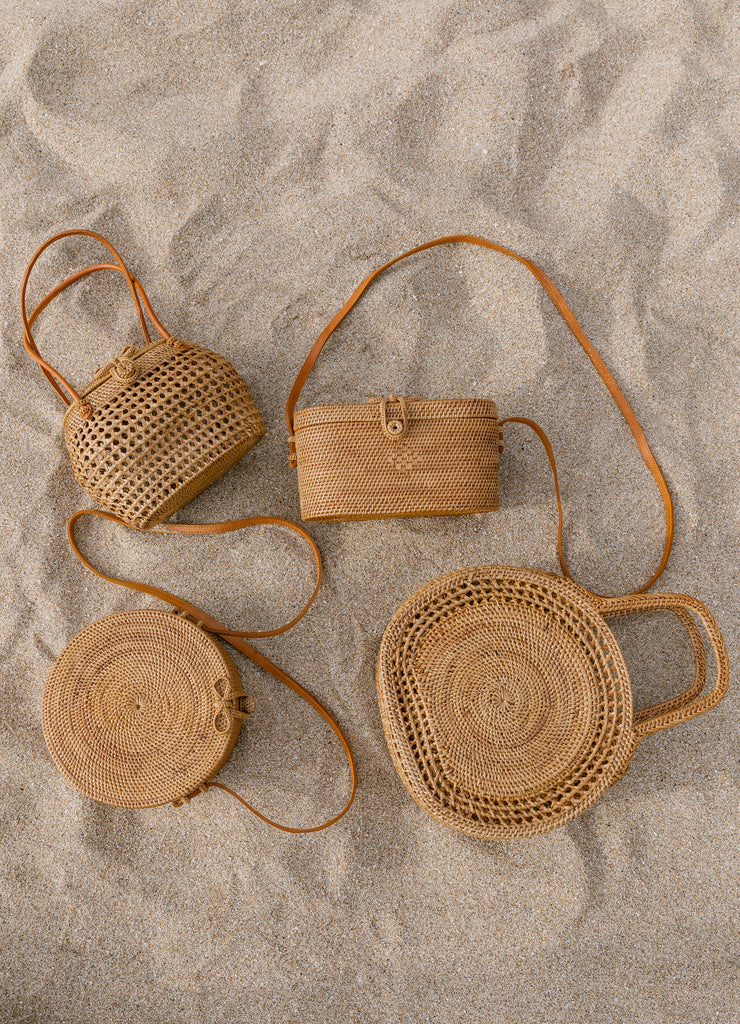 Collection of Tenganan Basket Bags against a sand background. - Saffron and Poe