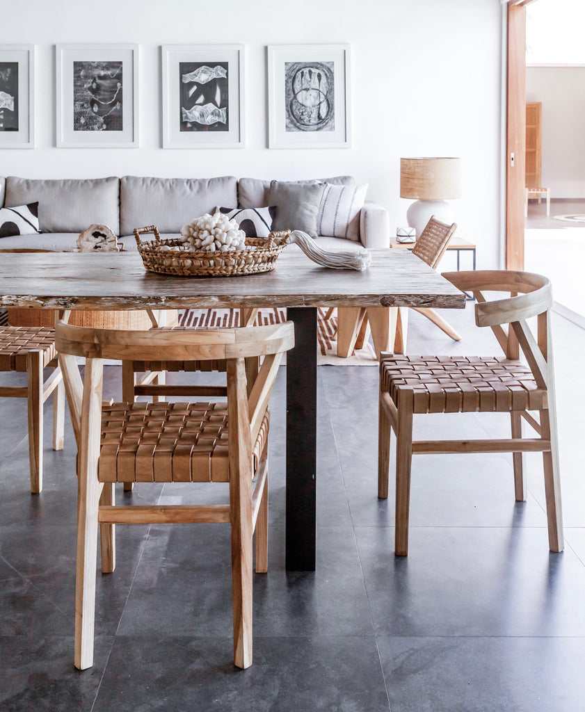 Three curved wood and woven beige leather dining chairs inspired by the wishbone Chair at kitchen table. Handcrafted in Bali with Teak wood and vegetable-tanned leather imported from Java. - Saffron and Poe