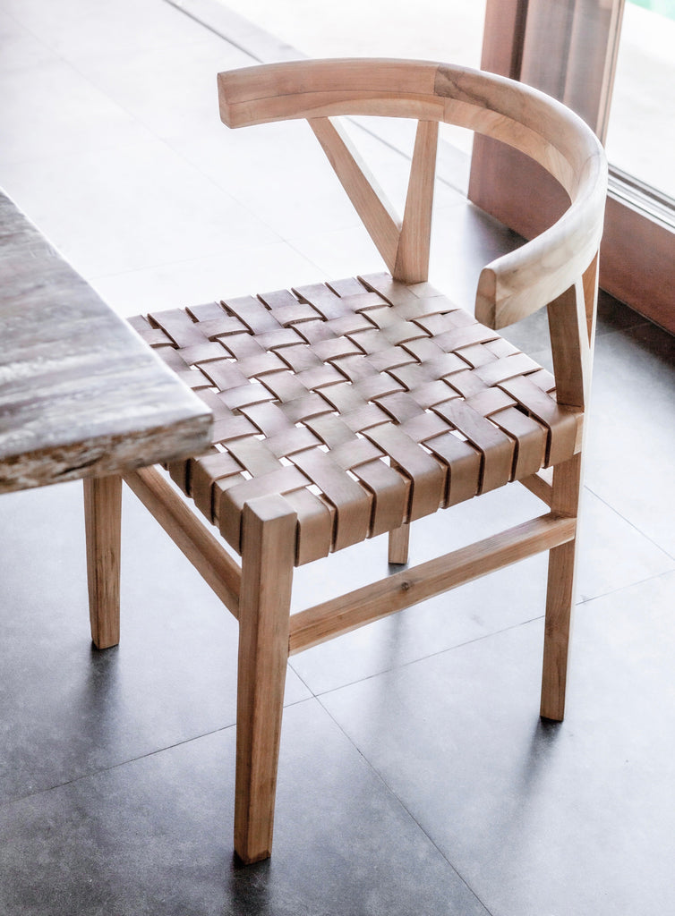 One curved wood and woven beige leather dining chair inspired by the wishbone Chair at the kitchen table. Handcrafted in Bali with Teak wood and vegetable-tanned leather imported from Java. - Saffron and Poe