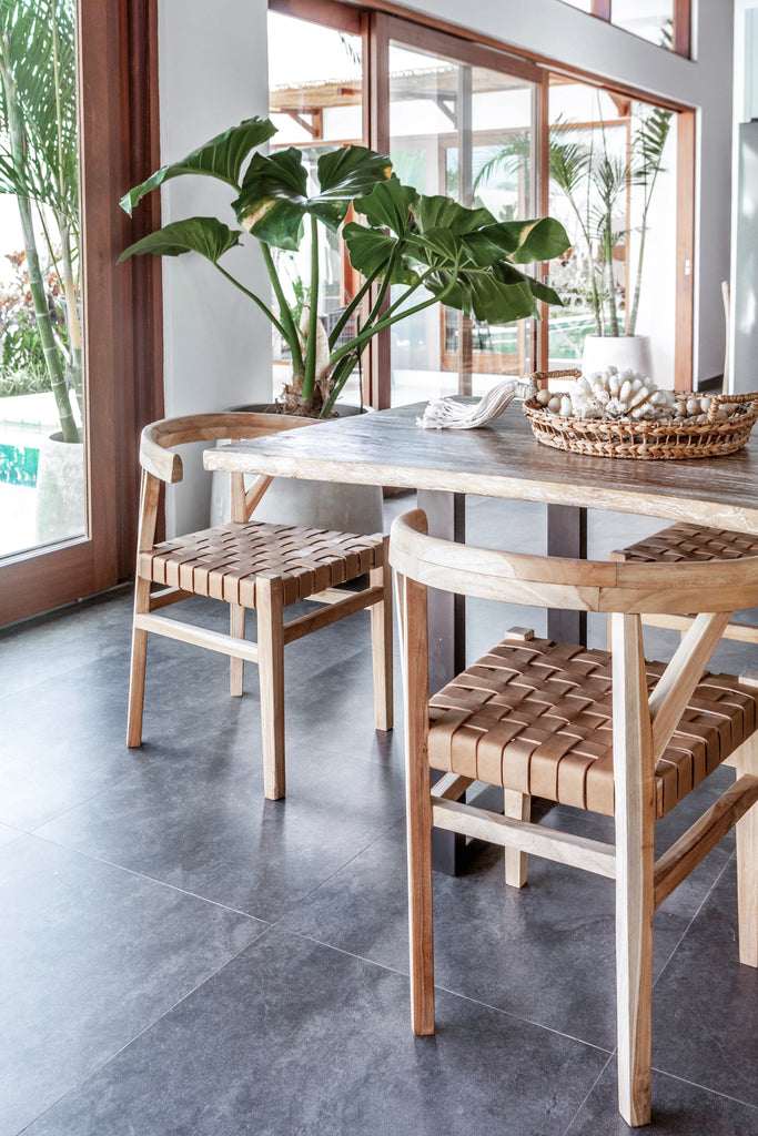 Two curved wood and woven beige leather dining chairs inspired by the wishbone Chair at the kitchen table with a plant. Handcrafted in Bali with Teak wood and vegetable-tanned leather imported from Java. - Saffron and Poe
