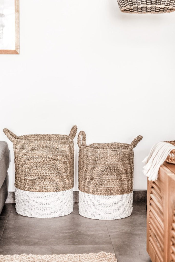 Two cream-colored with white base Structured Hyacinth storage baskets with handles against white wall. Handmade in Bali using natural water hyacinth  - Saffron and Poe