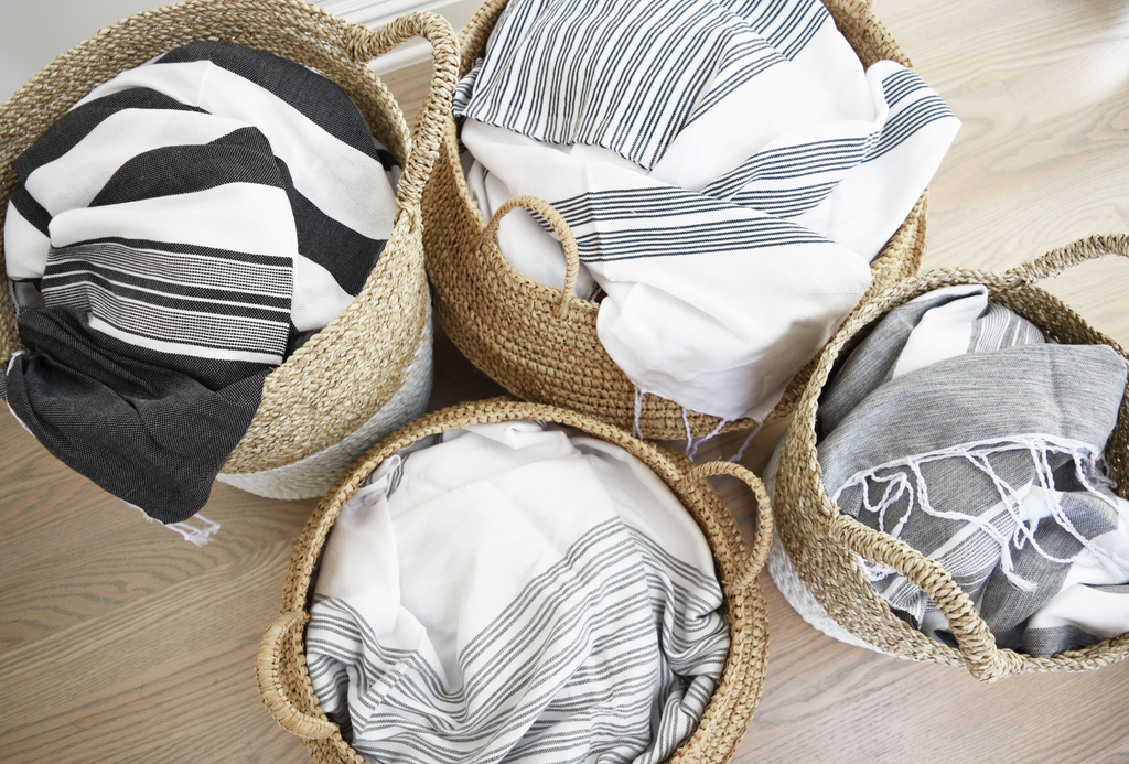 Four of our handwoven collapsible Hyacinth Storage Accent Baskets good for blankets, toys, shoes, collapsible, beautiful, and functional filled with blankets. Handmade in Bali using natural and white painted water hyacinth. - Saffron and Poe