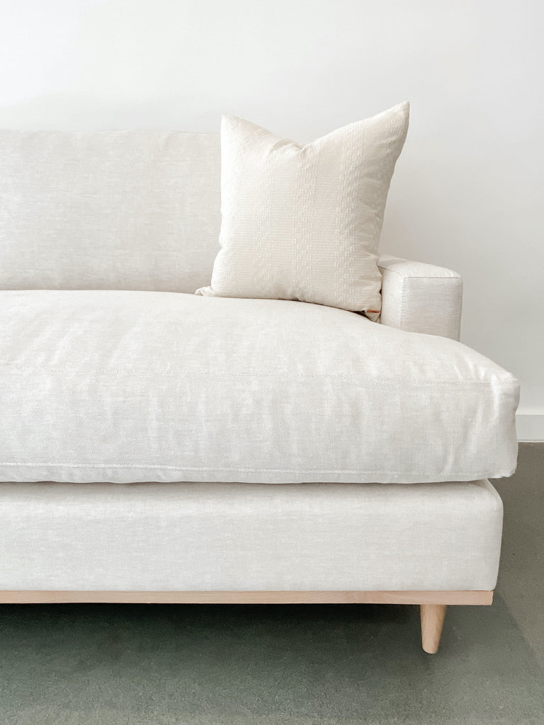 Close-up front view of contemporary linen and oak sofa on white background with concrete flooring.