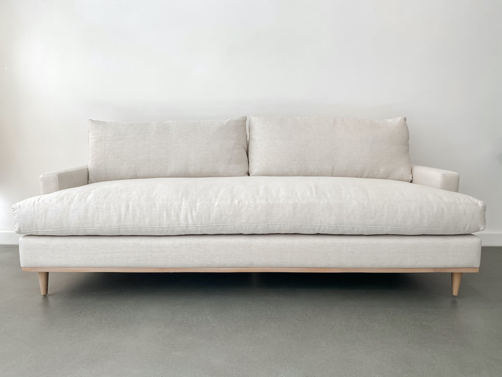 Front view of contemporary linen and oak sofa against white background on concrete floor.