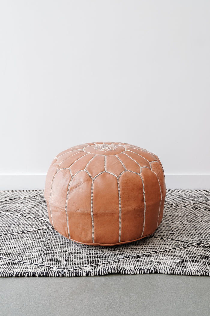 Front view of Embroidered Leather Moroccan Pouf on a Moroccan Kilim Rug against a white wall. - Saffron and Poe