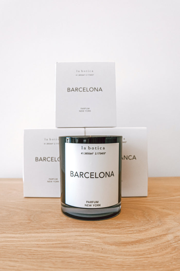 One La Botica Barcelona Candle set in front of three stacked Barcelona Candles against a white background with oak wood surface - Saffron and Poe
