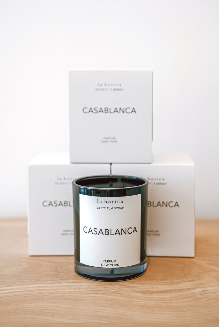One La Botica Casablanca Candle set in front of three stacked Casablanca Candles against a white background on a oak wood surface - Saffron and Poe