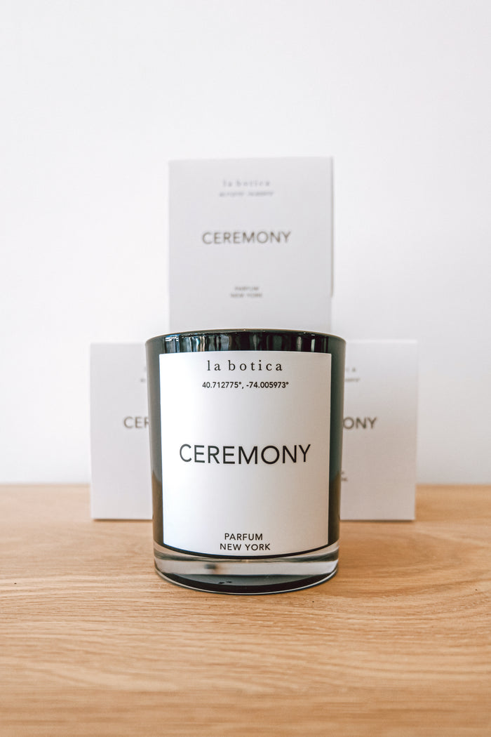 One La Botica Ceremony Candle in front of three stacked Ceremony Candles against a white background on an oak wood surface - Saffron and Poe