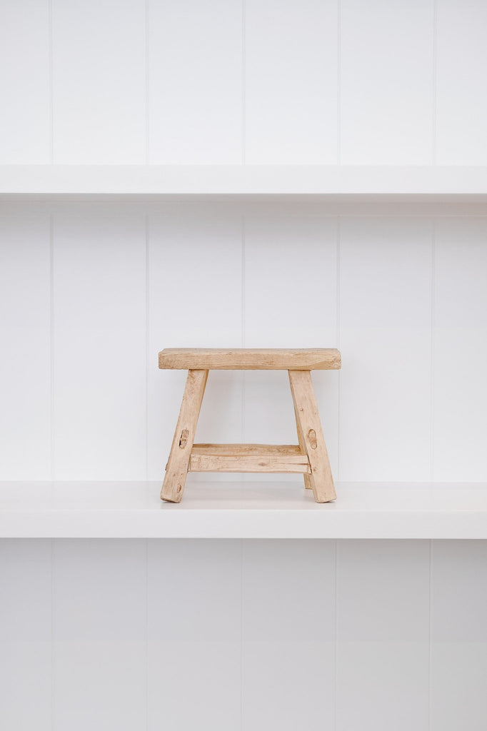 Front view of petite rectangle stool with white background on white shelf. - Saffron and Poe