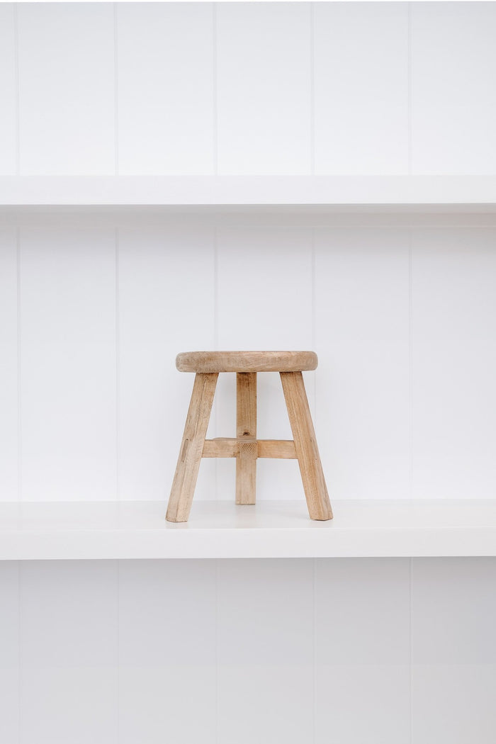 Front view of petite round stool on white shelf against white wood background. - Saffron and Poe