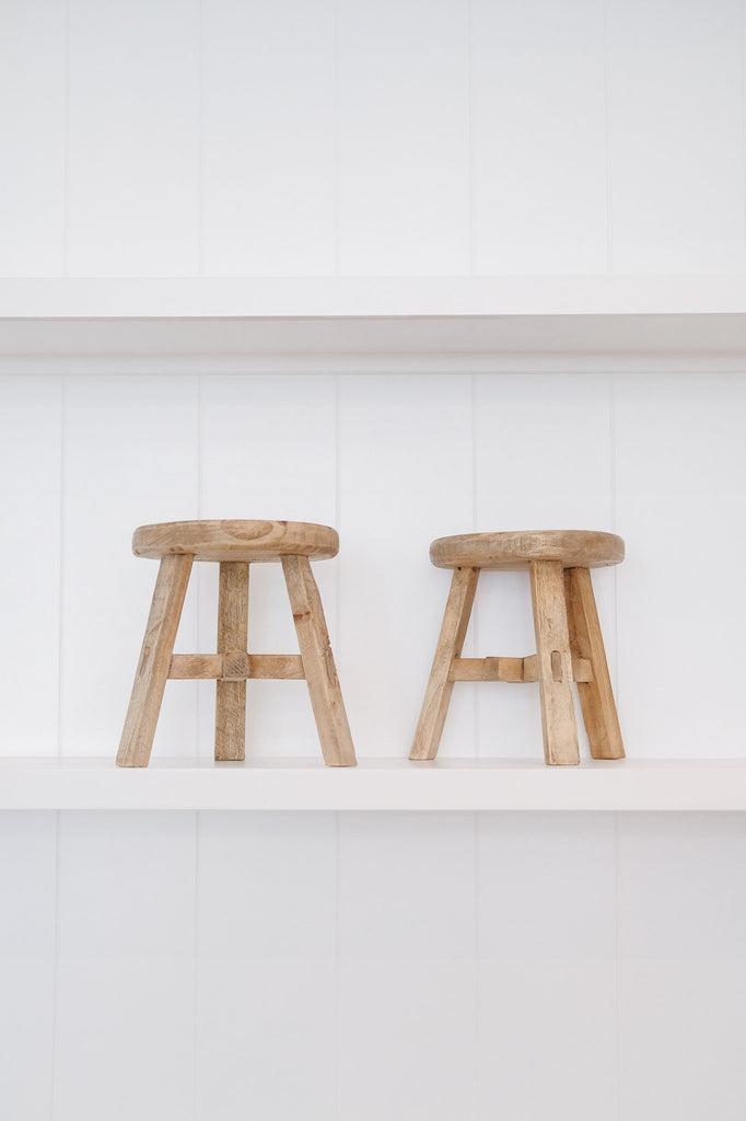 Two petite round stools against white background on white shelves. - Saffron and Poe