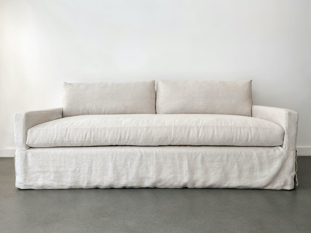 Front view of slipcover sofa in natural linen fabric against white background and concrete floor.