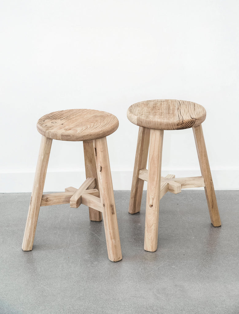 Two vintage round stools against white wall with concrete floor. - Saffron and Poe