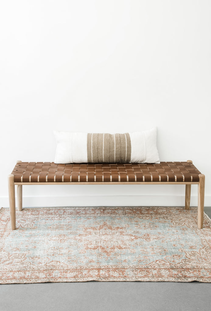 Teak framed Woven Leather Strap Bench styled over a rug with accent pillow. Furniture Handcrafted in Bali.- Saffron and Poe