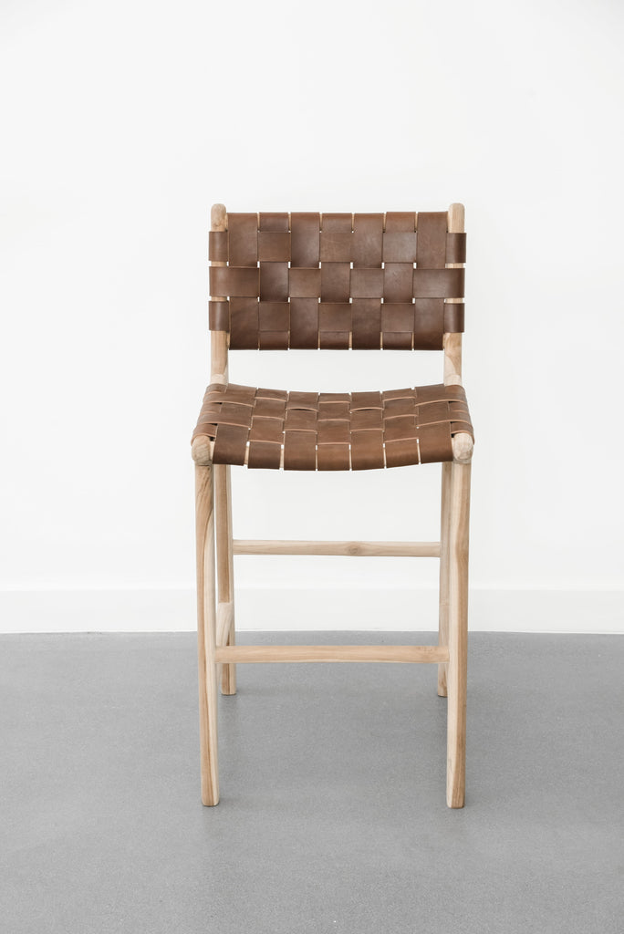 Front facing view of our Woven Leather Strap Counter Stool - Saddle on a white background. Handcrafted in Bali using teak wood and leather. - Saffron and Poe