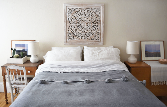 Boho styled bedroom with Moroccan Pom Bed Throw - Grey. Handwoven in Marrakech with wooden looms.- Saffron and Poe