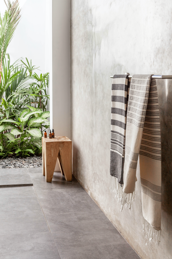 Lightweight Hammam Towel - Dark Grey and White Thick Stripe hanging in pool house with small accent table. Hand-woven in Marrakech using wooden looms. - Saffron and Poe