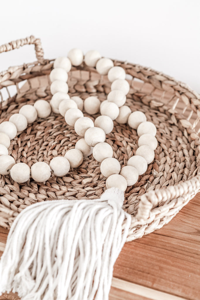 Top view of large Cream Tasseled Wooden Teak Bali Beads layed down in basket. Great for a necklace or an accessory handcrafted in Bali. -Saffron and Poe