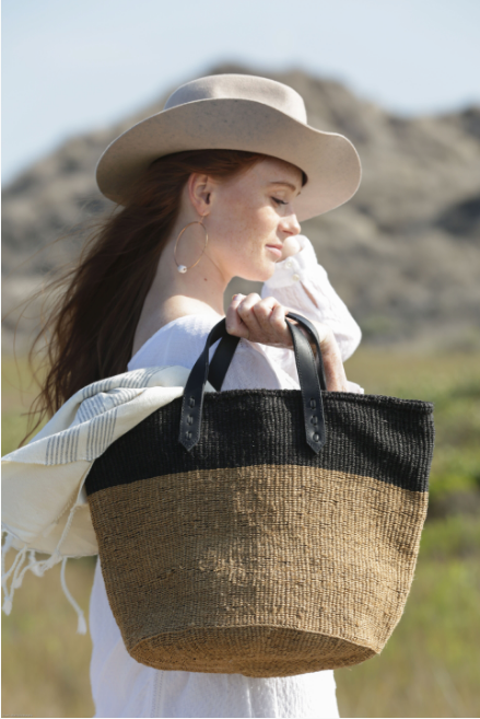 Woven Sisal Shopper bag on model at beach. Handwoven in Kenya with sisal fiber and leather. - Saffron and Poe