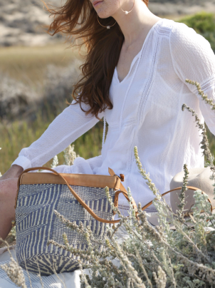 Woven Sisal and Leather Handbag - Blue and Cream laidback handbag handwoven in Kenya styled on model at the beach.- Saffron and Poe
