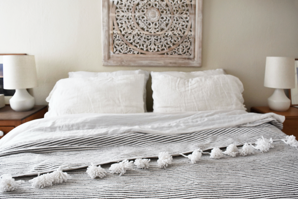 Bohemian bedroom linens styled with Moroccan Pom Bed Throw - Dark Grey and White Stripes. Hand-woven in Marrakech using wooden looms. - Saffron and Poe