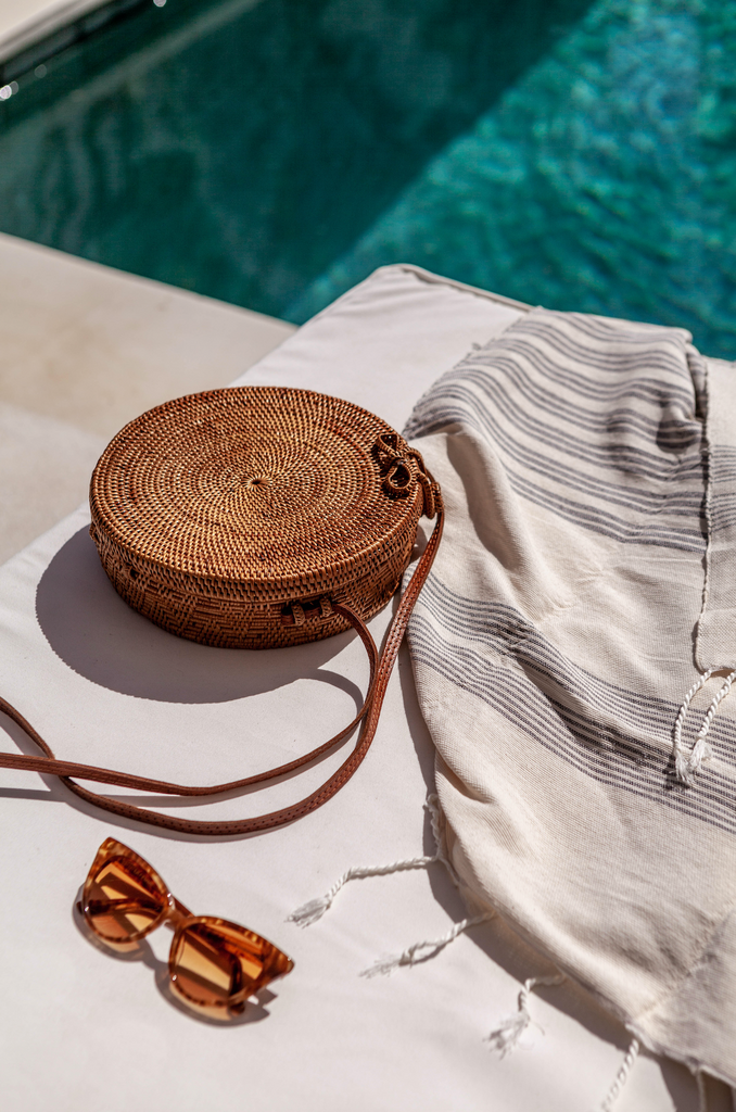 Pool laydown shot with glasses and towel plus casual, chic Tenganan Basket Crossbody Bag Round. Handmade in Tenganan, Bali using natural Ata reed and leather.  - Saffron and Poe